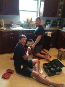 The men installing the garbage disposal.
